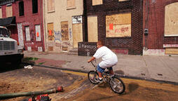 boy on bike in poor city neighborhood
