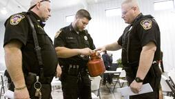 Police in Austin, Indiana look over biohazard container for disposal of syringes during HIV training session. Photo: AP/News and Tribune, Christopher Fryer